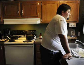 After losing their jobs, Scott and Kelly Nichols watched their finances and options dwindle, eventually making the tough decision to move their family to Kelly's mother's basement in Michigan. Photo: Washington Post  See article for further pictures
