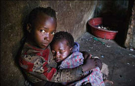 Seven-year-old Sinikiwe cradles her young brother Simba. Hunger stalks their family. Their local church, supported by the charity Tearfund provides what little food, clothing and seed they have. Photo: BBC