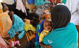 A woman holds her 6-month-old son, Abdul Rachman Salim, who is suffering from diarrhea and an eye infection, outside the Mercy Malaysia clinic in Zam Zam camp, in North Darfur. Aid agencies provide crucial services to 2.5 million displaced people in the region. Lynsey Addario/Los Angeles Times