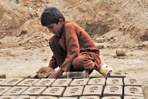 Photo of a child working in an Afgan brick kiln. Bonded labor in Afghanistan�s brick kilns is one of the most common forms of hazardous labor in the country. More than half of the brick kiln workers surveyed in a recent report by the International Labor Organization (ILO) were children. According to the ILO, the kilns rely on debt bondage: Workers and their families are tied to a kiln by the need to pay off loans taken out for basic necessities, medical expenses, weddings and funerals. Photo: IRIN