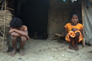 10-year-old Meena Devi, right, and her older brother Sunil, 11, outside their hut in Jhanwatola village, Bihar.