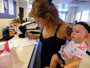 Laura Fritz, 27, left, with her daughter, Adalade Goudeseune, fills out a form at the Jefferson Action Center, an assistance center in the Denver suburb of Lakewood in July 2012.