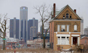 A single home in a block once filled with houses with the Detroit headquarters of General Motors in the distance. The company is thriving again. J.D. Pooley/Getty Images