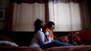 Photo of mother with child. A time to fight: Faced with the foreclosure of her home, Detroit resident LaKeisha Tuggle devised creative solutions to weather economic hardship. Photo: New York Times