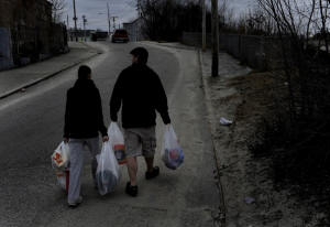 Photo of man and wife waling home with bags of groceries. Rhode Island town relies on food stamps: In Woonsocket, R.I., a third of the residents use SNAP, formerly known as food stamps, to pay for groceries. That means the businesses in the struggling town also rely on the program to survive. Photo: Michael S. Williamson/Washington Post