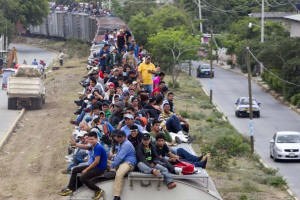 Dozens of Central American migrants riding through Mexico on the roof of a freight train