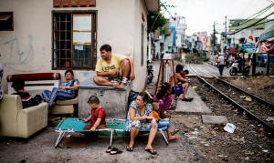 Five people sitting outside in a slum in Ho Chi Minh City, Vietnam. Wide dissatisfaction has followed the boom of the 1990s. Photo: Justin Mott/International Herald Tribune