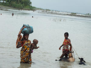 A mother and her children wading through floodwaters in Bangladesh. Photo: IRIN News