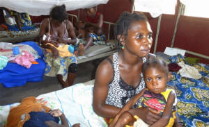 Woman sitting on hospital clinic bed with her malnourished child in the Central African Republic, where conflict has been widespread. Photo: Nicholas Long/IRIN