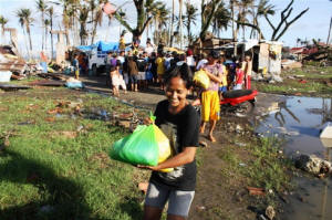 A woman and others collecting debris after  post-Typhoon Haiyan Photo: David Swanson/IRIN