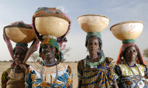 Four Niger women carrying food in baskets atop their heads.  Photograph: IFAD/David Rose