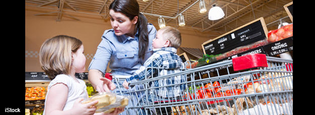 Woman grocery shopping with her two children.