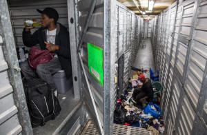 John Charles, 23, in his storage unit at Capital Self Storage while Michael Evans organizes his unit below. Photo: Evelyn Hockstein/The Washington Post