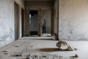 Picture of man standing in an unfinished apartment. Photo: Graham Crouch for The New York Times