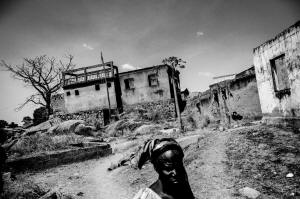 A woman walks in the burned down and completely destroyed Christian neighborhood of Jos, Nigeria. (Andy Spyra/Laif/Redux)