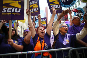 Fast-food workers and supporters gathered in Manhattan to watch a live video of the wage board�s decision. The governor hailed it as an example of New York�s progressiveness. Photo: Chang W. Lee/The New York Times
