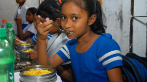 A young girl eats a fortified lunch through the school nutrition program. Photo: GAIN