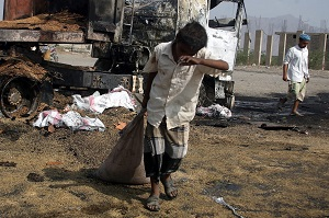 A Yemeni drags a sack away from a truck that was allegedly destroyed by an airstrike of the Saudi-led coalition targeting a wheat convoy. Photo: Abdul-Rahman Hwais/EPA