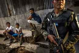 Soldier standing guard while children sit in Honduran city. Photo: IRIN