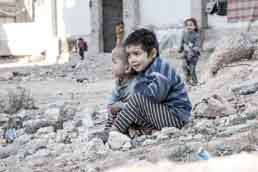 In Aleppo, Syria, four-year-old Esraa and her brother Waleed, three, sit on the ground near a shelter for internally displaced persons. Photo: UNICEF/UN013175/Al-Issa