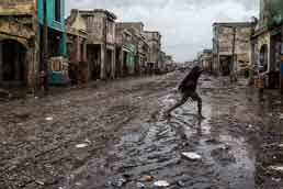 A woman crosses a muddy street in downtown Port-au-Prince after Hurricane Matthew hit Haiti on 4 October 2016, bringing heavy rains and winds. Photo: UN/MINUSTAH/Logan Abassi