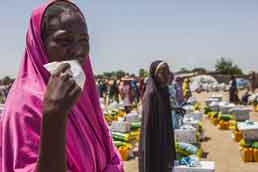 Women wait for food to be distributed at an internally displaced persons camp in Monguno, Nigeria. Photo: Jane Hahn/The Washington Post