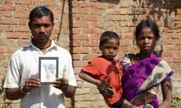 Devganga Sawra, seen here with his wife Sunder and younger son, holds an image of their son Vishwarnam, who died of malnutrition in September. Photograph: Vidhi Doshi/The Guardian